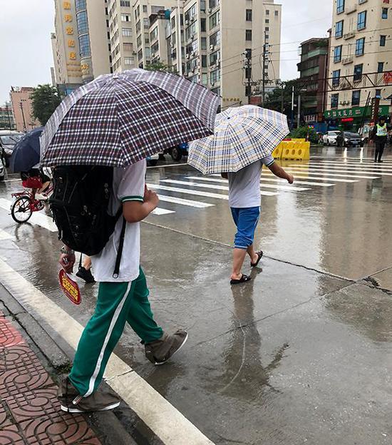 学生穿着拖鞋或戴着防水鞋套走出考场。