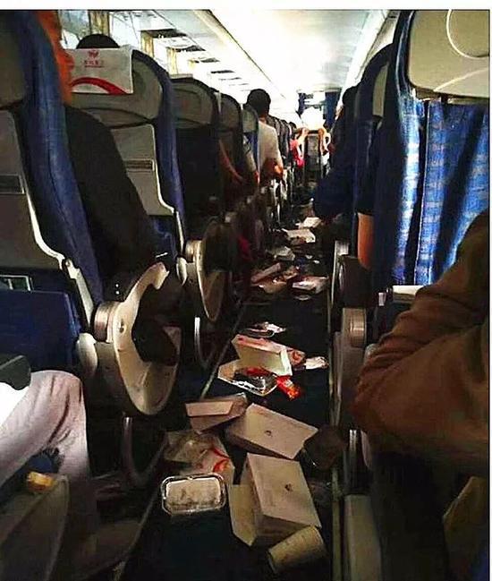 飞机剧烈颠簸后,过道上落满了餐盒