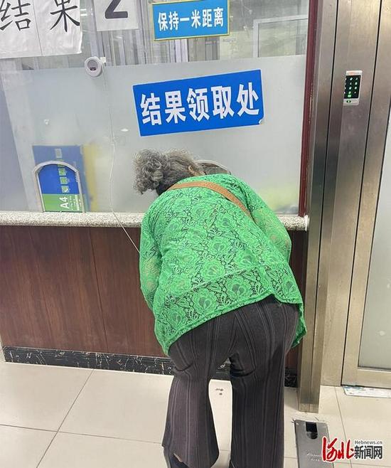 """圖為一名老人""""卑躬屈膝""""在窗口前領取化驗結果。 網民楊女士供圖"""