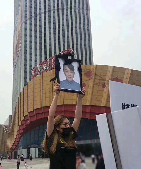 女儿雅雅举着妈妈的遗像,在南京万达茂门前讨要说法。