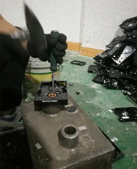工人正在拆解硬盘。图:梁宙/摄