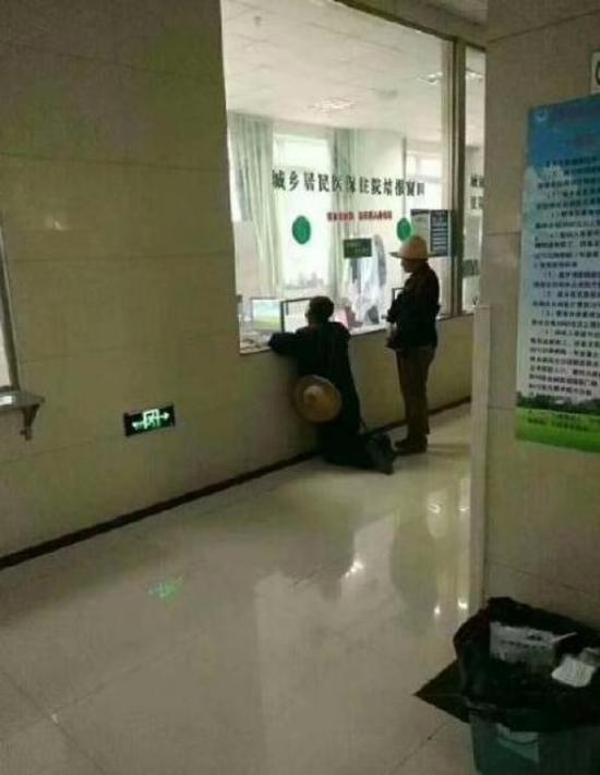 """""""老人在甘肃礼县第一人民医院缴费窗口前双膝跪地""""的照片"""