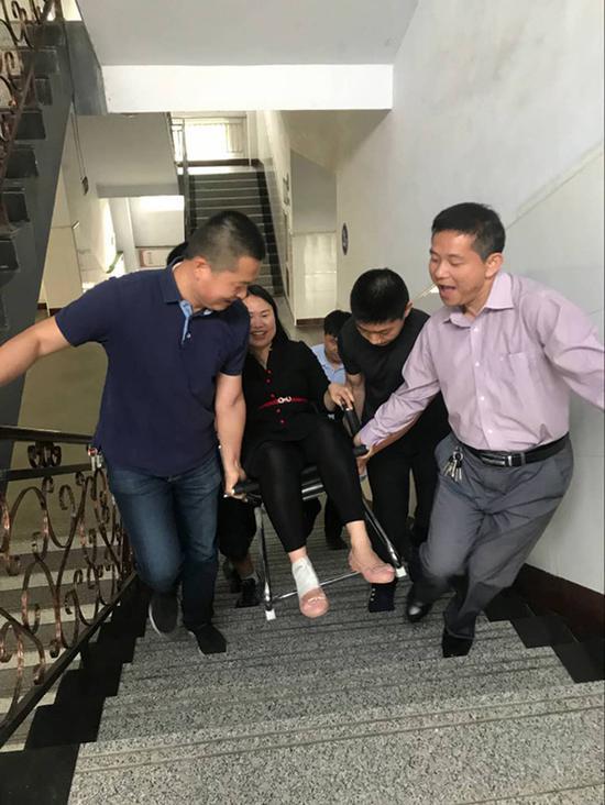 男教师们用椅子抬着王娟上楼梯。受访者供图