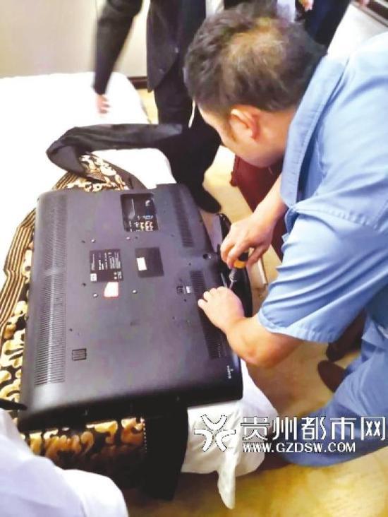 酒店工程部人员拆开电视机后壳检查。贵州都市报 图