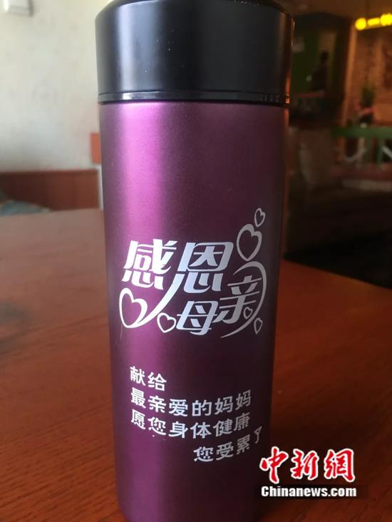 凌先生随身带着女儿送给妈妈的母亲节礼物——保温杯(赵强/摄)