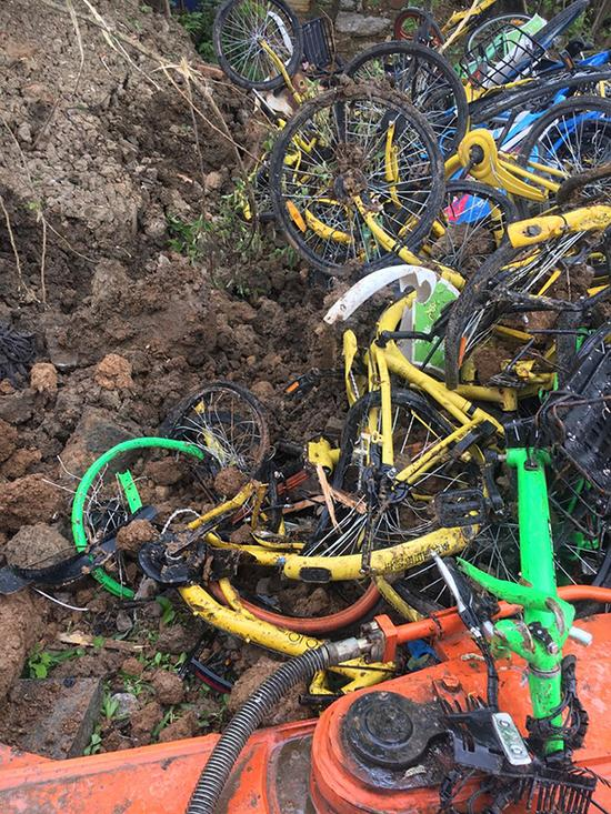 """4月12日,铁心桥街道停车办已安置人员将被土""""埋葬""""的共享单车掘出,大多车辆破坏严沉。 磅礴消息记者 陈卓 图"""