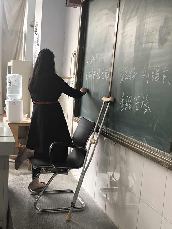 王娟一条腿跪在板凳上给学生们进行考前复习。受访者供图