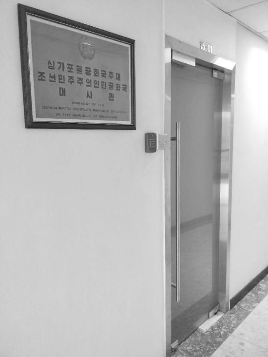 """位于新加坡市中心""""谐街中心大厦""""15层的朝鲜驻新使馆看上去很低调,门口只有一块印着朝鲜国徽及朝英双语的""""朝鲜民主主义人民共和国驻新加坡共和国大使馆""""字样的铜牌。赵觉��摄"""