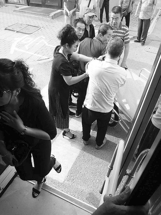 司机和乘客将老人送往医院。