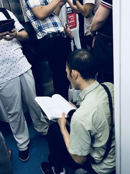 连续两天遇到这个读《强化学习精要》的人,他每天都自己带小板凳上地铁。