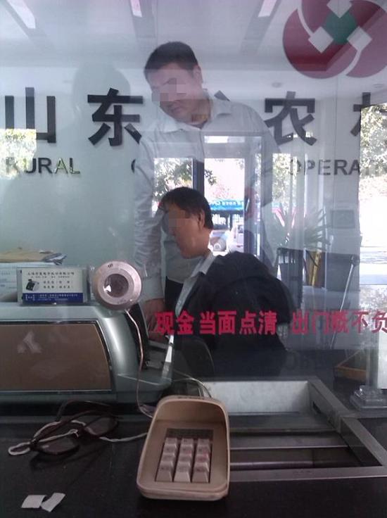 一名受害人在滨城区农信社渤海五路分社存钱时,曾拍下柜台内的李某及赵某。当事人供图