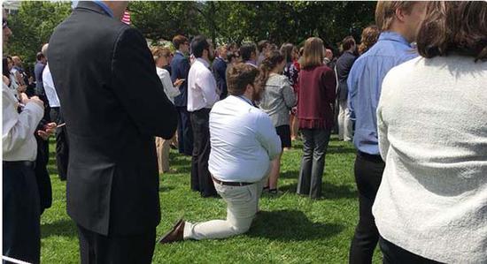 白宫草坪前,一男子单膝跪地。
