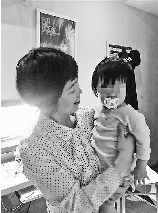 检察官杨琴抱着梁静的二女儿,满眼怜惜和疼爱。