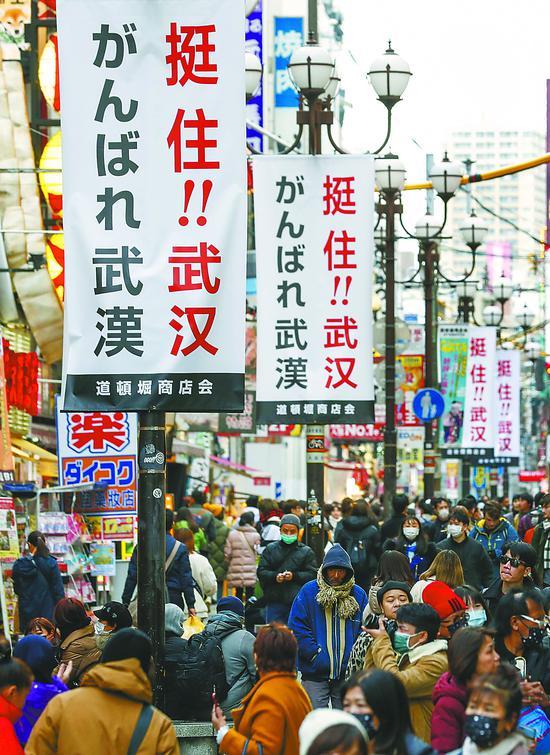 """10日,日本大阪道顿堀商圈的街道上挂起中日双语的""""挺住!!武 汉""""标语。近日,日本各界以不同形式为中国抗击新冠疫情加油鼓劲。"""