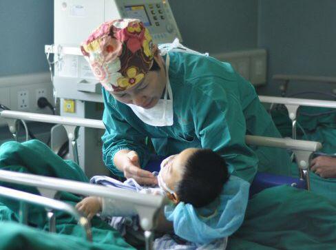 麻醉护士厉萌怀抱着刚刚手术结束的孩子,他正在麻醉复苏中