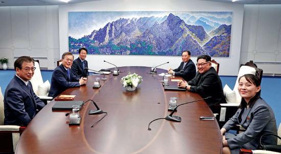 4月27日,韩国总统文在寅(左二)和朝鲜国务委员会委员长金正恩(右二)在板门店举行会晤。右一为金与正。图/韩朝首脑会晤媒体报道团