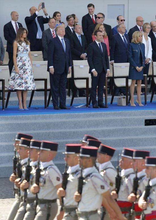 资料图片:2017年7月14日,在法国巴黎香榭丽舍大街,法国总统马克龙(前右二)和夫人布丽吉特(前右一)、美国总统特朗普(前左二)和夫人梅拉尼娅(前左一)出席阅兵仪式。新华社/美联