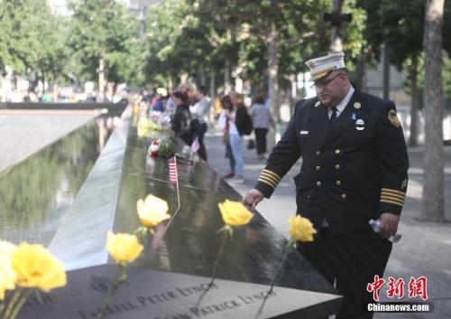 资料图:2017年9月11日,美国纽约市举行9·11事件16周年纪念仪式,近千名遇难者家属聚集在世贸中心遗址广场,悼念逝去的亲友。图为一位消防员站在刻有遇难者姓名的矮墙边。 中新社记者 马德林 摄