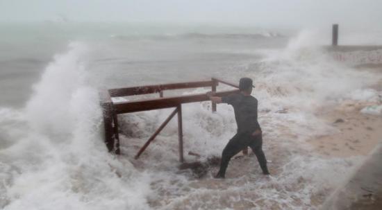 在飓风中抢救家当的餐厅老板 图源:路透社