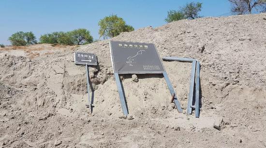揽海阁公厕指示标扔在沙丘边