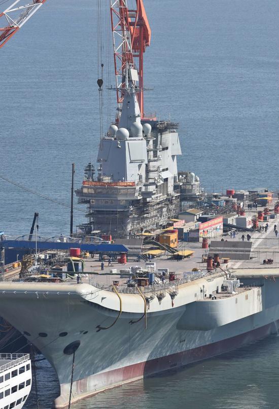 3月16日,辽宁大连,施工人员用各种设备在甲板平台四周、舰岛及舰舷上全面作业。