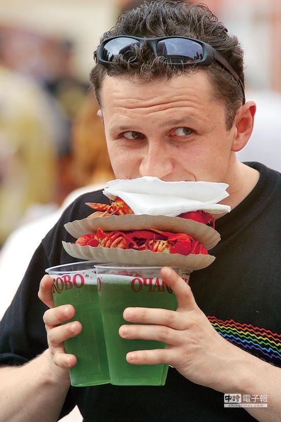 游客在莫斯科手捧饮料和小龙虾,图片来自中时电子报。