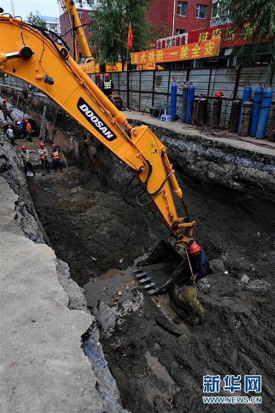 7月15日,在长春市南关区永长路,工人们在地沟内清理淤泥和积水。