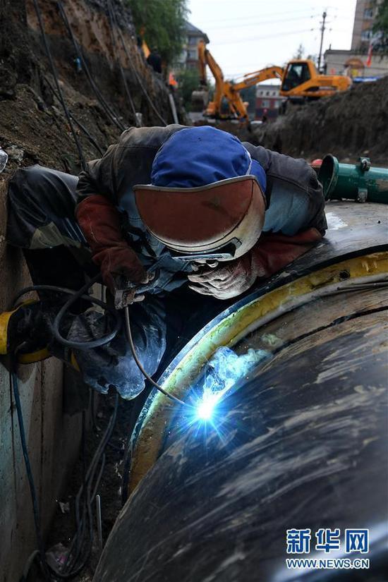7月15日,在长春市南关区永长路,焊工刘刚蜷缩在供热管道与墙壁间,焊接管道接缝。