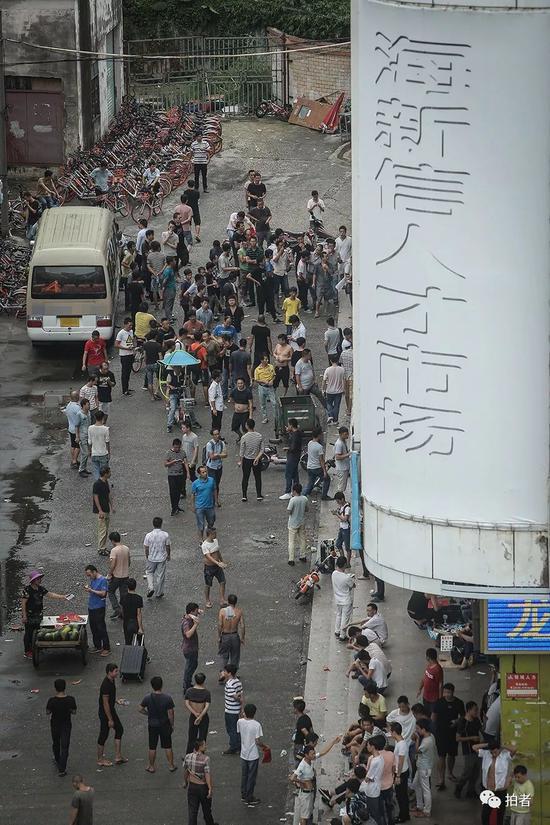 """△ 8月14日早晨5点40分,海新信人才市场旁的街道上,已经围满了前来""""抢""""薪水日结工作的打工者。这里就是三和人力市场。"""