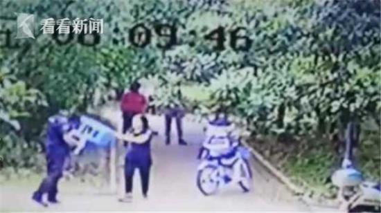 """小区监控显示:浙江金华市""""南国名城""""小区一名保安被女业主用木棍抡、塑料凳砸。 看看新闻网视频截图"""
