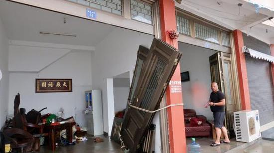 大门被海浪打破后,居民暂时将门绑在门柱上。澎湃新闻记者 杨亚东 摄
