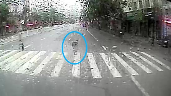一名女性行人在斑马线上,给雨中让行的公交司机鞠躬道谢。 十堰公交车监控视频截图