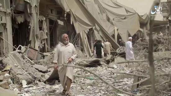 叙利亚城市拉卡居民在评估空袭造成的破坏。(美联社)