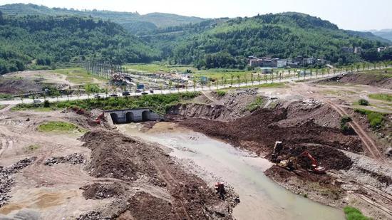 挖掘机正在拆除水磨溪河道内的夯土挡墙。            王守城摄