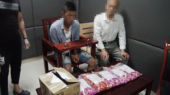 犯罪嫌疑人(中)取货时被警方抓获。九龙坡警方供图