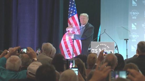 图为特朗普在演讲最后拥抱美国国旗。(来源:白宫视频截图)