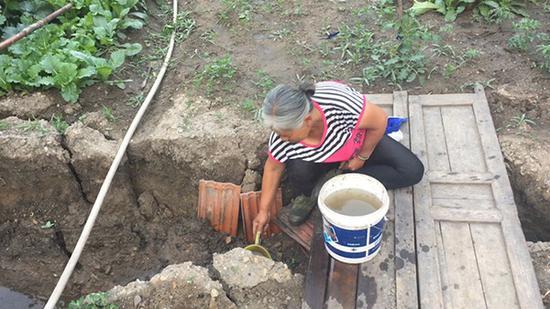 因为村庄停水,村民只好用山缝里溢出的水。