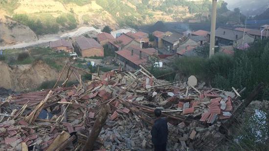 村民李志强站在倒塌的房屋废墟前面。
