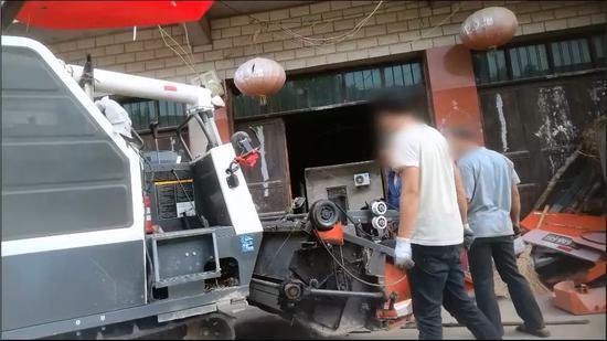 (注:工人正在翻新农机。)