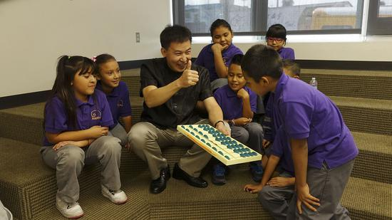 (远赴美国帮助美国孩子学算术的中国珠算老师。)
