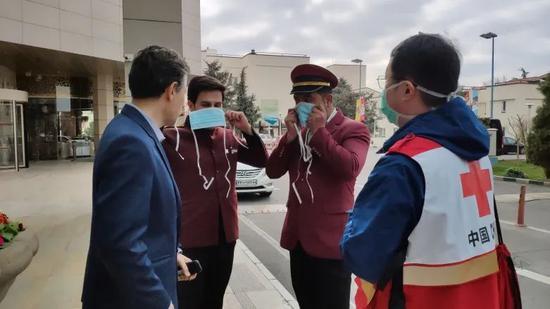 ▲伊朗旅社工作人員向中國專家叨教口罩的佩戴方法