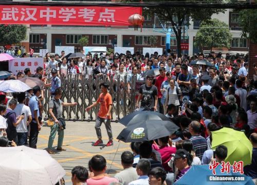 资料图:2017年6月7日,武汉市武汉中学考点,走出考点的考生和等待的家长汇合。 中新社记者 张畅 摄