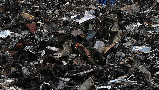 """2011年9月9日,浙江台州椒江港内,一名工人守着小山般的""""洋垃圾""""酣然入梦。图片来源:视觉中国"""