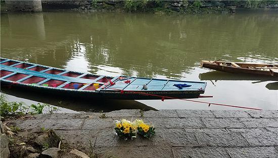 2018-06-23上午,有人在事发水域岸边摆上鲜花白酒祭奠遇难者。摄影:翟星理