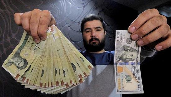 资料图:货币兑换商展示伊朗货币里亚尔与美元的兑换比例 图片来源:视觉中国