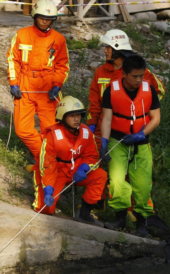 这是在上海市庙行镇一水闸附近,蒋雨航(前左)在搜救打捞任务中的资料照片(2009年5月7日摄)。新华社发(澎湃新闻记者赵昀 摄)