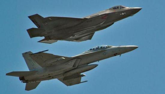 """资料图片:F/A-18F""""超级大黄蜂""""(双座型)与F-35C隐身战机编队飞行。(图片来源于网络)"""