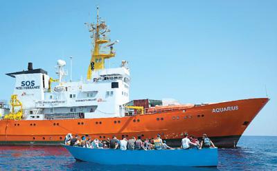 """西班牙首相佩德罗·桑切斯6月11日指示东部港口巴伦西亚允许载有629名难民的法国民间难民救援船""""阿奎里厄斯""""号入港。图为2017年8月29日在利比亚海域拍摄的法国民间难民救援船""""阿奎里厄斯""""号和一艘坐满难民的小木船。新华社/美联"""