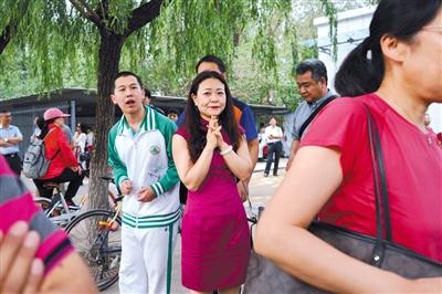 一零一中学,一名穿着旗袍的家长看着孩子进入考场。新京报记者 郑新洽 摄