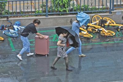 """昨日早晨,受台风""""白鹿""""影响,厦门市出现风雨天气,给市民出行带来不便。图/视觉中国"""